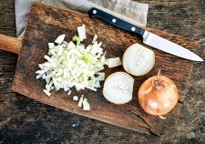 42628228 - chopped onions on wooden cutting board, top view